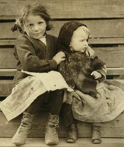 Two little girls sitting on a wooden staircase.